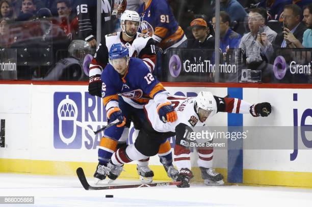 Josh Bailey of the New York Islanders and Anthony Duclair of the Arizona Coyotes battle for the puck during the first period at the Barclays Center...