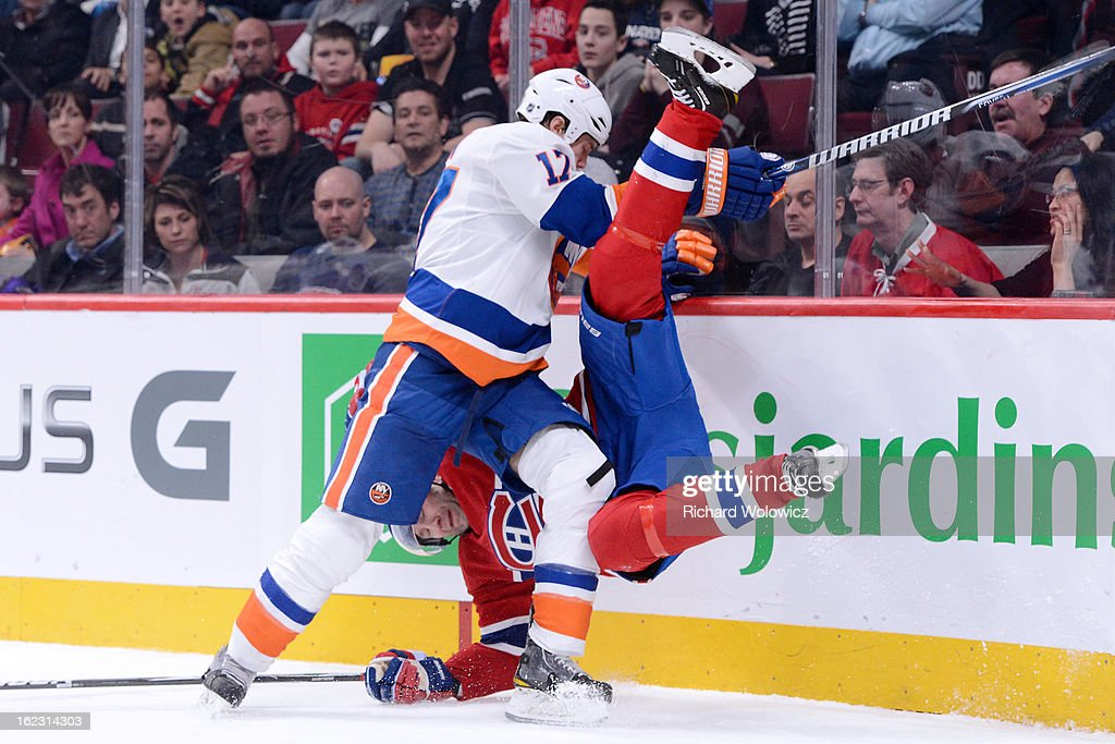 Josh Bailey #12 of the New York Islanders checks Erik Cole #72 of the Montreal Canadiens during the NHL game at the Bell Centre on February 21, 2013 in Montreal, Quebec, Canada.