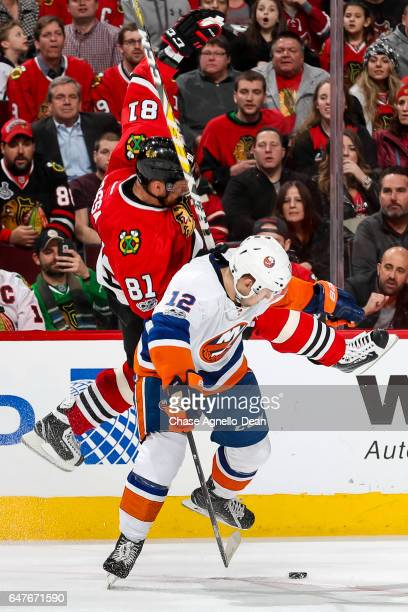 Josh Bailey of the New York Islanders hits Marian Hossa of the Chicago Blackhawks in overtime at the United Center on March 3 2017 in Chicago...