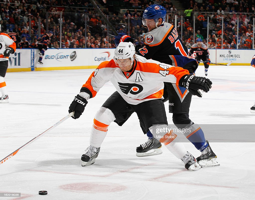 Josh Bailey #12 of the New York Islanders is held off by Kimmo Timonen #44 of the Philadelphia Flyers at Nassau Veterans Memorial Coliseum on February 18, 2013 in Uniondale, New York.