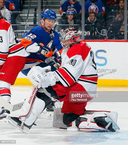 Josh Bailey of the New York Islanders skates against Cam Ward of the Carolina Hurricanes during an NHL hockey game at Barclays Center on February 4...