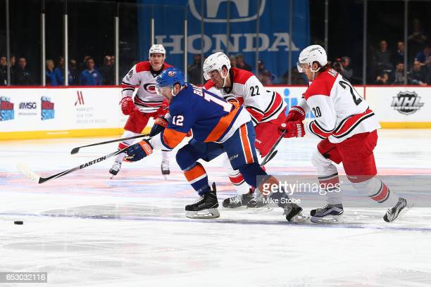 Josh Bailey of the New York Islanders skates for the puck against Sebastian Aho and Brett Pesce of the Carolina Hurricanes at the Barclays Center on...