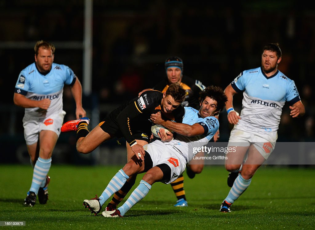 Josh Bassett of London Wasps is tackled by Mathieu Belie of Bayonne during the Amlin Challenge Cup round two match between London Wasps and Bayonne at Adams Park on October 17, 2013 in High Wycombe, England.