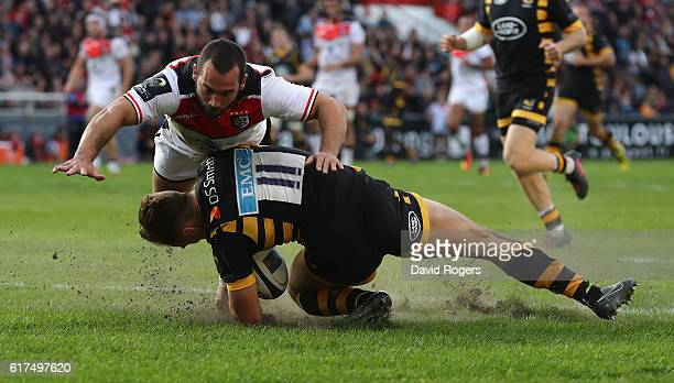 Josh Bassett of Wasps falls awkwardly as his foot is caught in the turf after diving to score their first try during the European Champions Cup match...