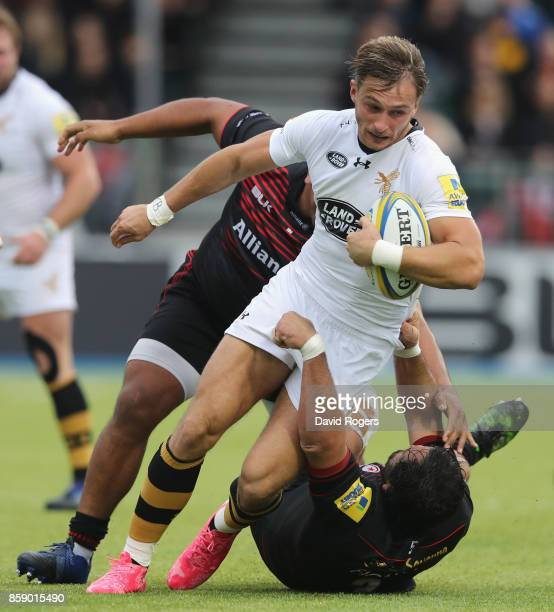 Josh Bassett of Wasps is tackled by Juan Figallo and Mako Vunipola during the Aviva Premiership match between Saracens and Wasps at Allianz Park on...