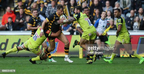 Josh Bassett of Wasps is tackled by Mike Williams and Adam Thompstone during the Aviva Premiership semi final match between Wasps and Leicester...