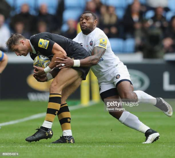 Josh Bassett of Wasps is tackled by Semesa Rokoduguni during the Aviva Premiership match between Wasps and Bath Rugby at The Ricoh Arena on October 1...