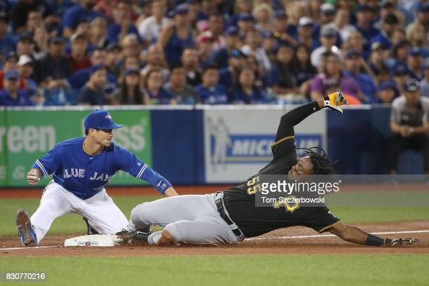 Josh Bell of the Pittsburgh Pirates slides into third base with a triple in the second inning during MLB game action as Darwin Barney of the Toronto...
