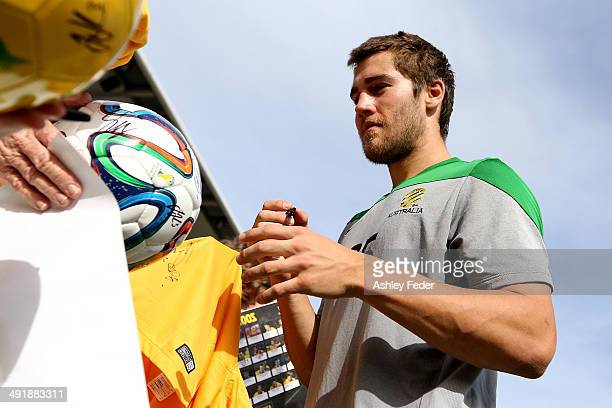Josh Brillante of the of Socceroos signs autographs for fans during the Australian Socceroos Fan Day Training Session at Bluetongue Stadium on May 18...