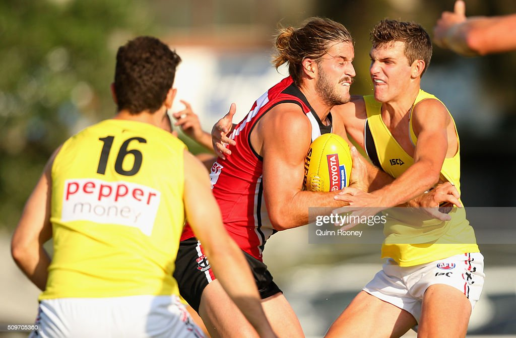 Josh Bruce of the Saints fends off a tackle during the St Kilda Saints AFL Intra-Club Match at Trevor Barker Beach Oval on February 12, 2016 in Melbourne, Australia.