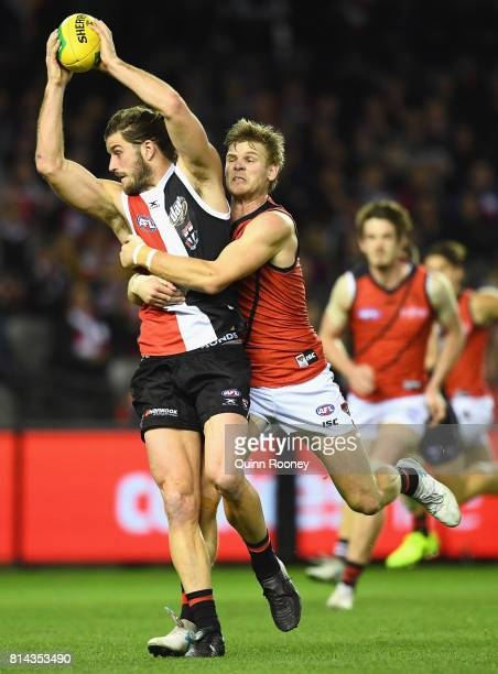Josh Bruce of the Saints is tackled by Michael Hurley of the Bombers during the round 17 AFL match between the St Kilda Saints and the Essendon...