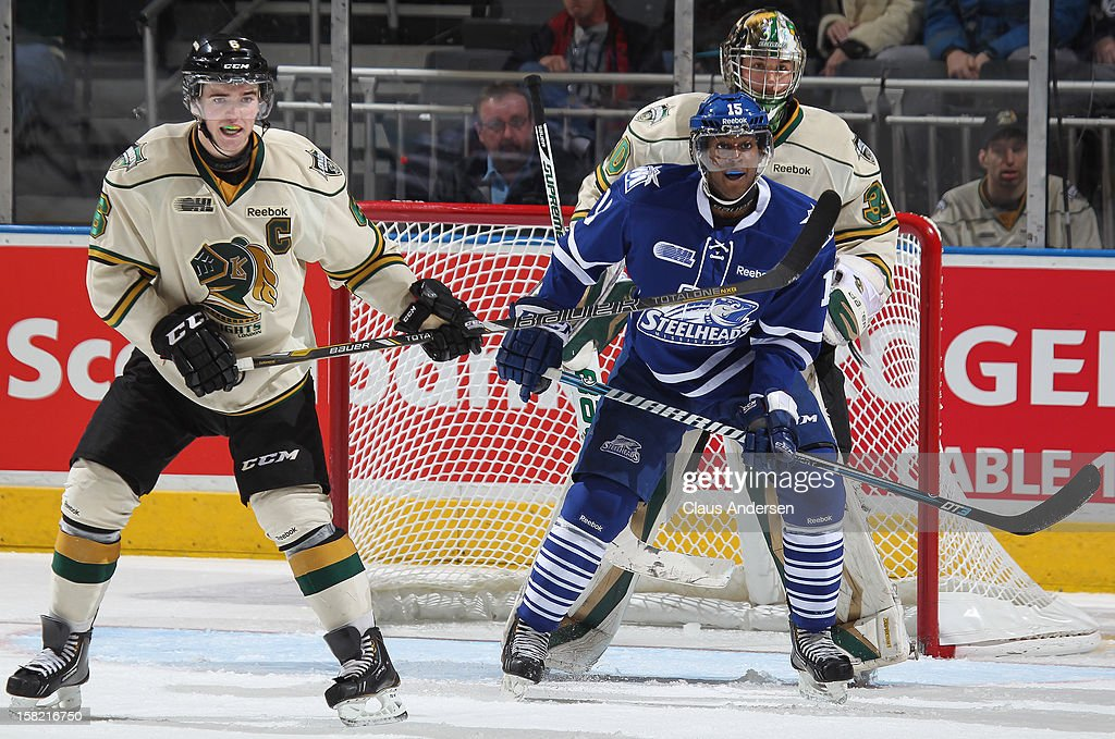 Josh Burnside #15 of the Mississauga Steelheads waits to tip a shot between Scott Harrington #6 and Kevin Bailie #30 of the London Knights in an OHL game on December 9, 2012 at the Budweiser Gardens in London, Ontario, Canada. The Knights defeated the Steelheads 5-2 and tied their franchise record of 18 straight wins.