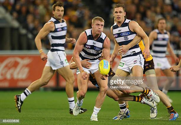 Josh Caddy of the Cats handballs whilst being tackled by Jordan Lewis of the Hawks during the round 22 AFL match between the Hawthorn Hawks and the...