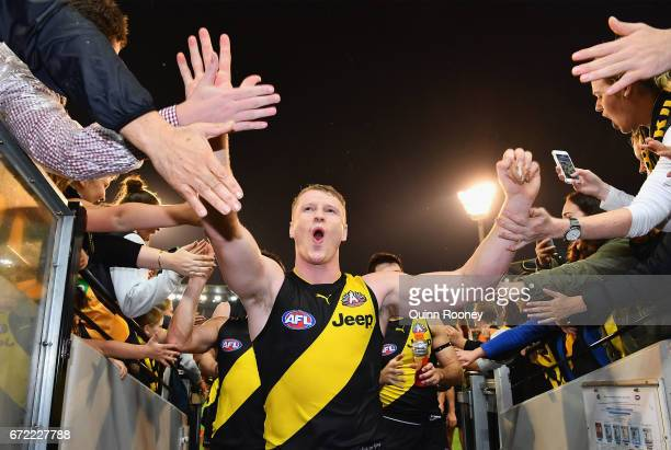 Josh Caddy of the Tigers high fives fans after winning the round five AFL match between the Richmond Tigers and the Melbourne Demons at Melbourne...