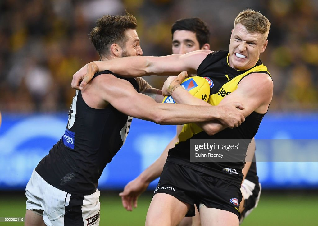 Josh Caddy of the Tigers is tackled by Dale Thomas of the Blues during the round 14 AFL match between the Richmond Tigers and the Carlton Blues at Melbourne Cricket Ground on June 25, 2017 in Melbourne, Australia.