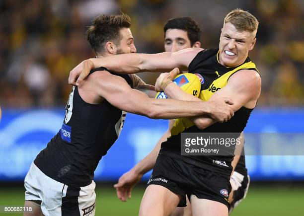 Josh Caddy of the Tigers is tackled by Dale Thomas of the Blues during the round 14 AFL match between the Richmond Tigers and the Carlton Blues at...