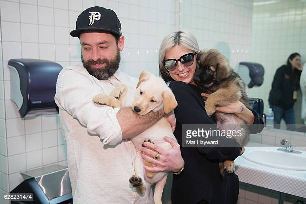 Josh Carter and Sarah Barthel of Phantogram hold puppies brought by animal rescue organization Motley Zoo backstage during Deck The Hall Ball hosted...