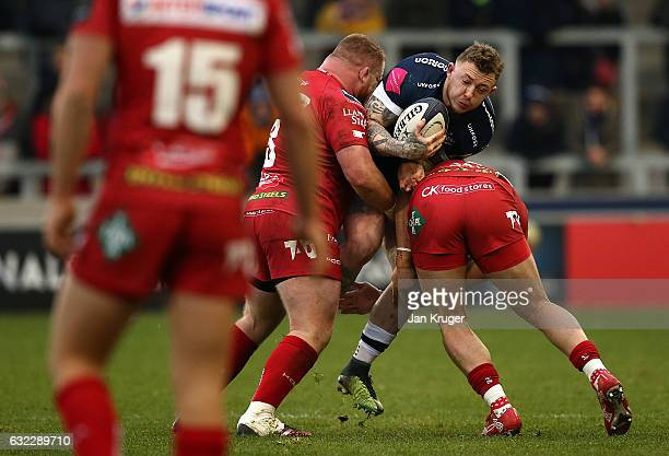 Josh Charnley of Sale Sharks is tackled by Samson Lee of Scarlets during the European Rugby Champions Cup match between Sale Sharks and Scarlets at...