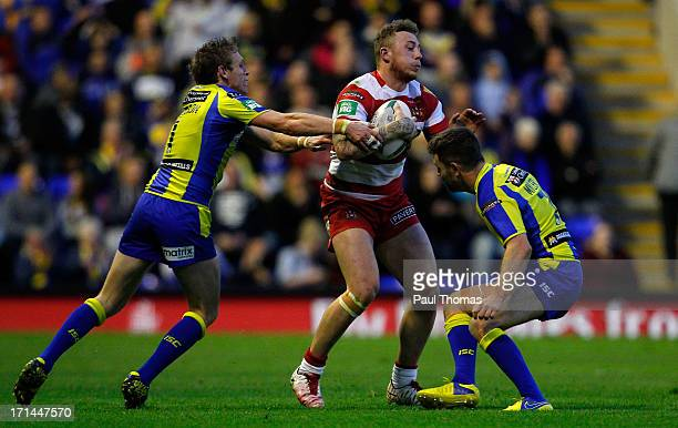 Josh Charnley of Wigan is challenged by Brett Hodgson and Richie Myler of Warrington during the Super League match between Warrington Wolves and...