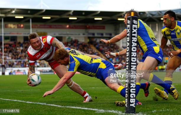 Josh Charnley of Wigan is tackled by Chris Riley of Warrington during the Super League match between Warrington Wolves and Wigan Warriors at the...