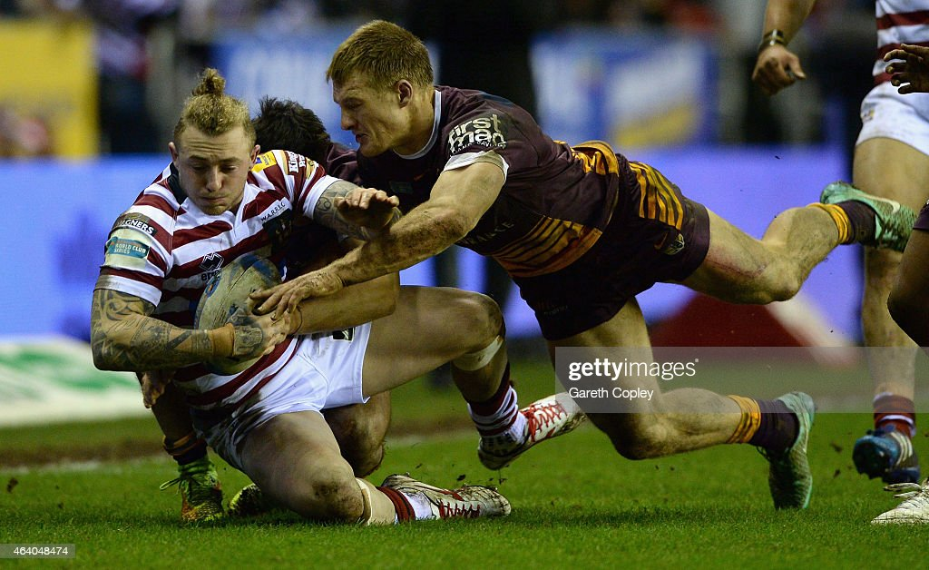 Josh Charnley of Wigan Warriors is tackled by Aaron Whitchurch of Brisbane Broncos during the World Club Series match between Wigan Warriors and...