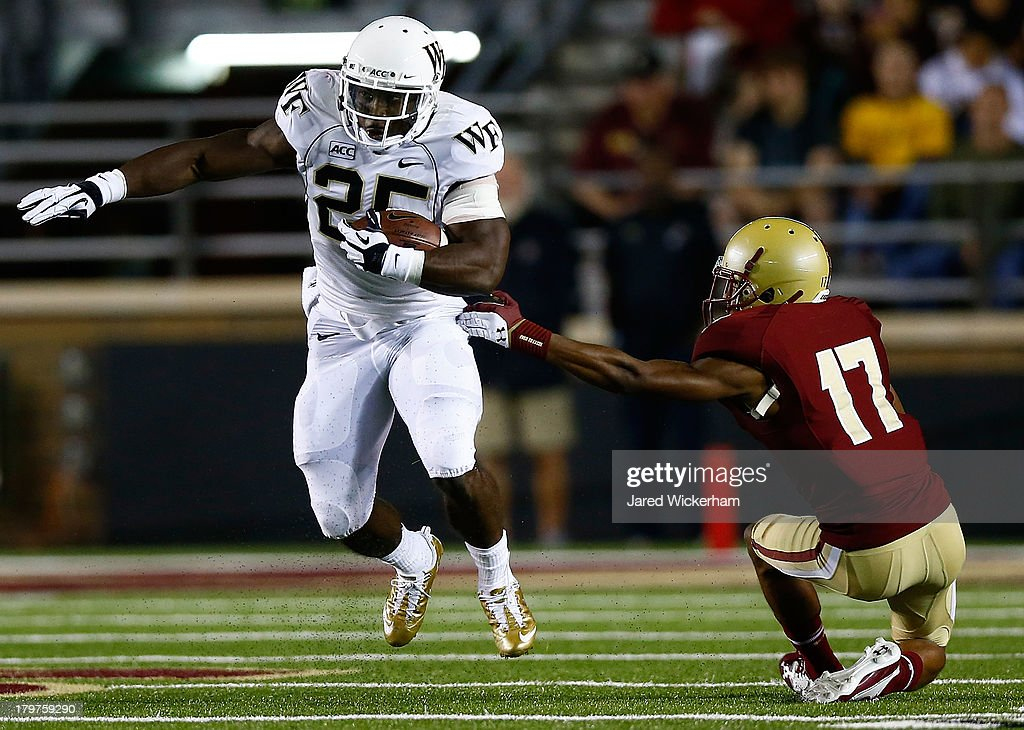 Josh D. Harris #25 of the Wake Forest Demon Deacons runs with the ball past Bryce Jones #17 of the Boston College Eagles during the game on September 6, 2013 at Alumni Stadium in Chestnut Hill, Massachusetts.