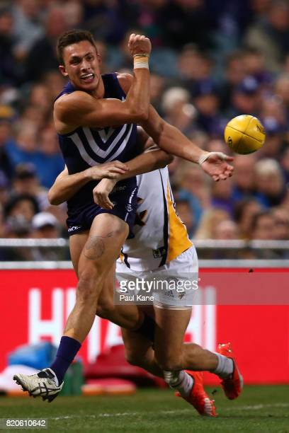 Josh Deluca of the Dockers gets a handball away while being tackled by Luke Hodge of the Hawks during the round 18 AFL match between the Fremantle...