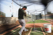 Josh Donaldson of the Oakland Athletics hits of a batting tee in the cage prior to a spring training game against the Milwaukee Brewers at Phoenix...