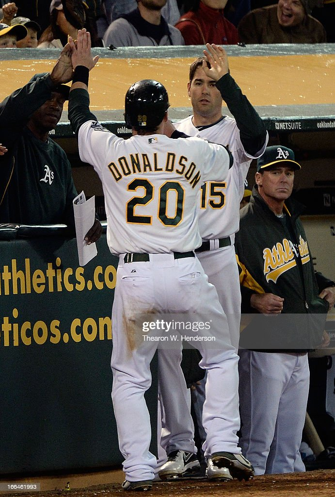Josh Donaldson #20 of the Oakland Athletics is congratulated by teammate <a gi-track='captionPersonalityLinkClicked' href=/galleries/search?phrase=Seth+Smith&family=editorial&specificpeople=3190174 ng-click='$event.stopPropagation()'>Seth Smith</a> #15 after Donaldson scored on an RBI single from teammate Coco Crisp #4 against the Detroit Tigers in the seventh inning at O.co Coliseum on April 12, 2013 in Oakland, California.