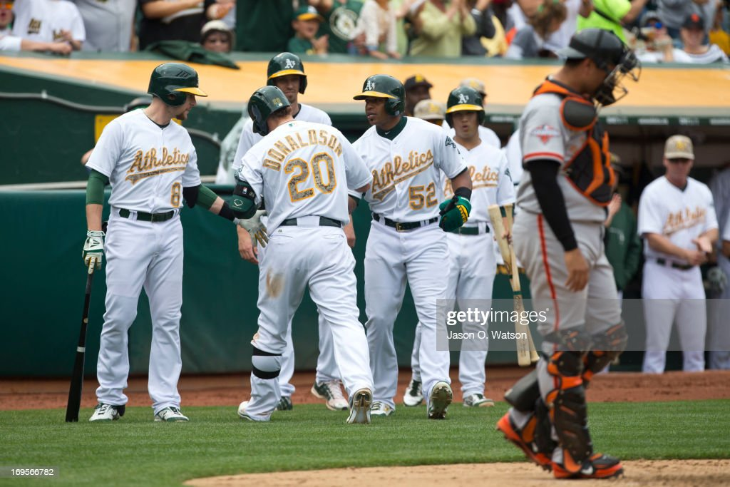 Josh Donaldson #20 of the Oakland Athletics is congratulated by teammates after hitting a two run home run off of Madison Bumgarner (not pictured) of the San Francisco Giants during the fourth inning of the interleague game at O.co Coliseum on May 27, 2013 in Oakland, California.