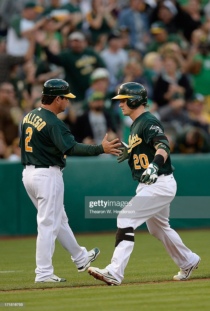 Josh Donaldson #20 of the Oakland Athletics is congratulated by third base coach Mike Gallego #2 as he rounds third base after Donaldson hit a two-run homer in the third inning against the Cincinnati Reds at O.co Coliseum on June 25, 2013 in Oakland, California.