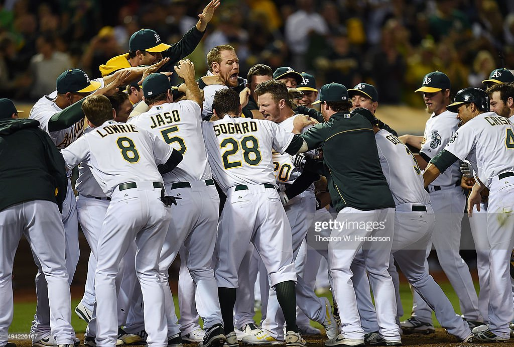 Josh Donaldson of the Oakland Athletics is met at home plate by teammates after hitting a threerun walkoff homer to defeat the Detroit Tigers 31 at...