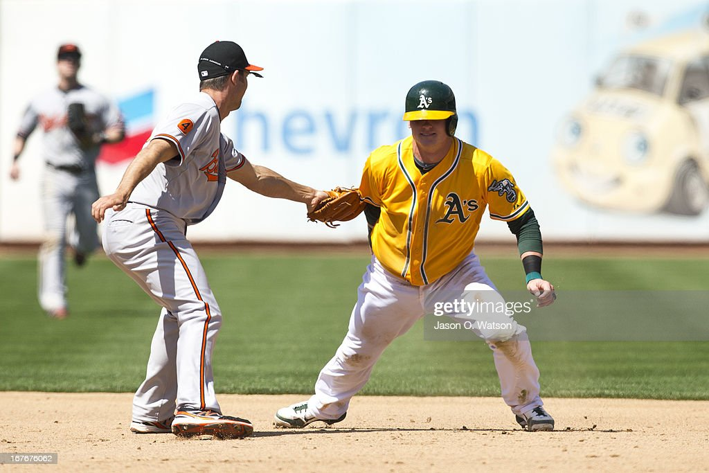Josh Donaldson #20 of the Oakland Athletics is tagged out at second base by J.J. Hardy #2 of the Baltimore Orioles after a pick off play during the sixth inning at O.co Coliseum on April 27, 2013 in Oakland, California.