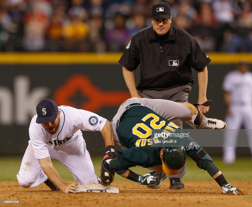 <a gi-track='captionPersonalityLinkClicked' href=/galleries/search?phrase=Josh+Donaldson&family=editorial&specificpeople=4959442 ng-click='$event.stopPropagation()'>Josh Donaldson</a> #20 of the Oakland Athletics is tagged out by second baseman <a gi-track='captionPersonalityLinkClicked' href=/galleries/search?phrase=Dustin+Ackley&family=editorial&specificpeople=4352278 ng-click='$event.stopPropagation()'>Dustin Ackley</a> #13 of the Seattle Mariners as he tries to stretch a single into a double in the ninth inning at Safeco Field on May 11, 2013 in Seattle, Washington.