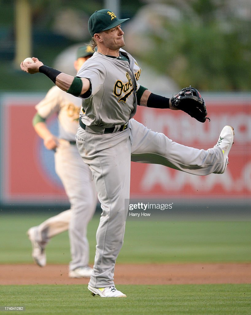 Josh Donaldson #20 of the Oakland Athletics makes a throwing error to first base on a J.B. Shuck #39 of the Los Angeles Angels single during the first inning at Angel Stadium of Anaheim on July 19, 2013 in Anaheim, California. Shuck ended up at second base on the error.