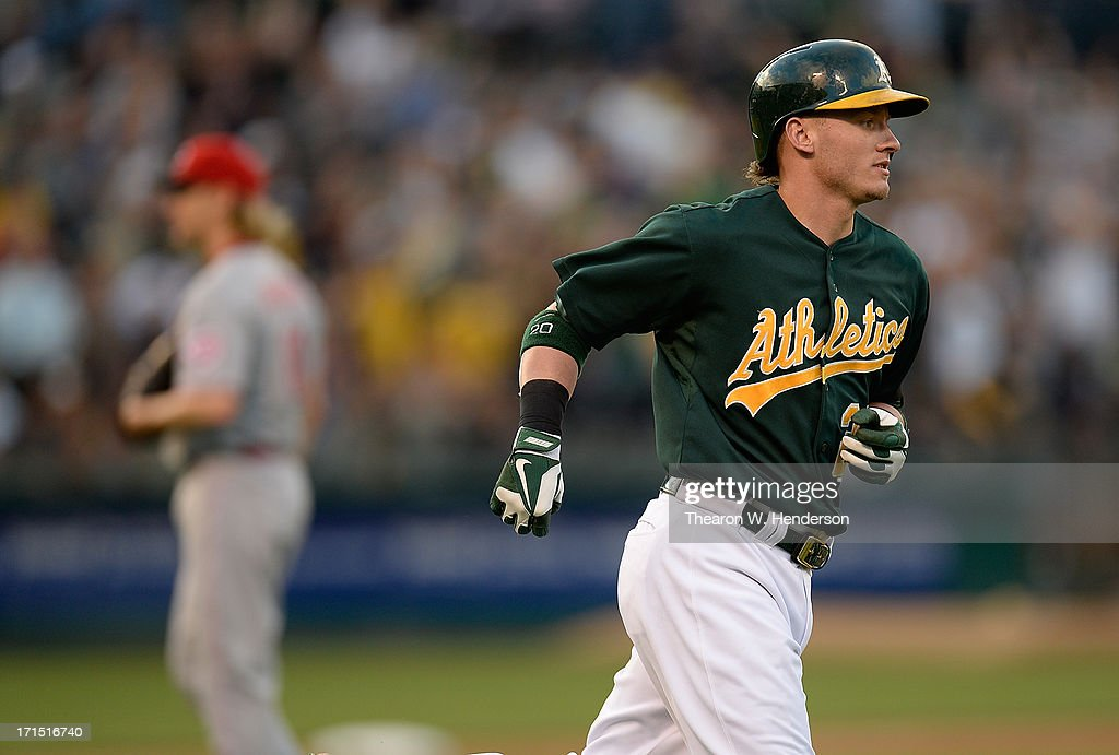 Josh Donaldson #20 of the Oakland Athletics trots around the bases after hitting a two-run homer as pitcher Bronson Arroyo #61 of the Cincinnati Reds looks on in the third inning at O.co Coliseum on June 25, 2013 in Oakland, California.