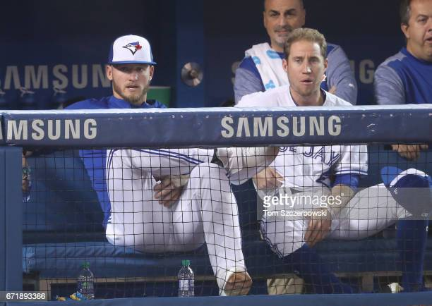 Josh Donaldson of the Toronto Blue Jays and Ty Kelly look on from the top step of the dugout during MLB game action against the Boston Red Sox at...