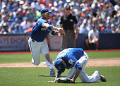 Josh Donaldson of the Toronto Blue Jays cannot throw out the baserunner as Jesse Chavez ducks in the sixth inning during MLB game action as Shawn...
