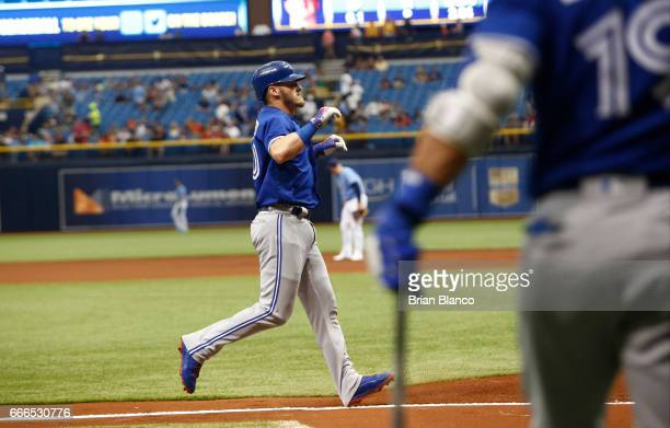 Josh Donaldson of the Toronto Blue Jays celebrates as he runs in to cross home plate after hitting a home run off of pitcher Jake Odorizzi of the...