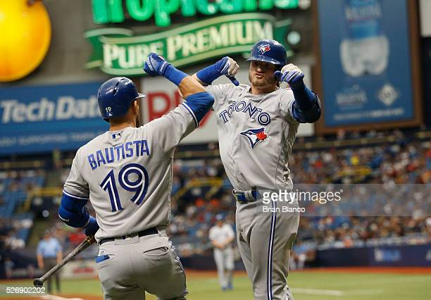 Josh Donaldson of the Toronto Blue Jays celebrates his home run with teammate Jose Bautista during the fourth inning of a game against the Tampa Bay...