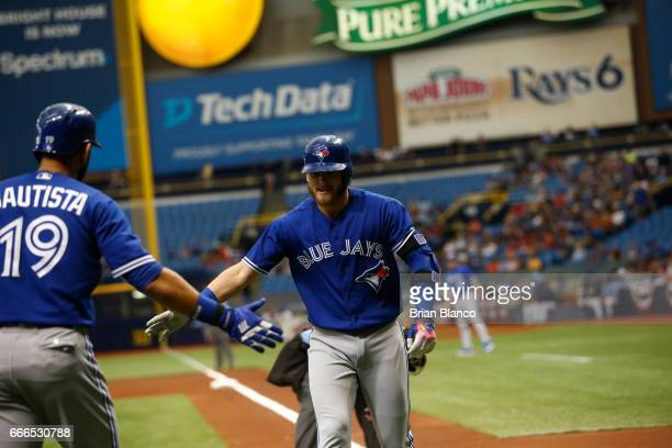 Josh Donaldson of the Toronto Blue Jays celebrates his home run with teammate Jose Bautista during the first inning of a game against the Tampa Bay...