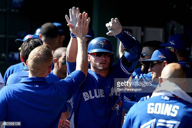 Josh Donaldson of the Toronto Blue Jays celebrates in the dugout after hitting a tworun home run in the first inning against the Texas Rangers in...
