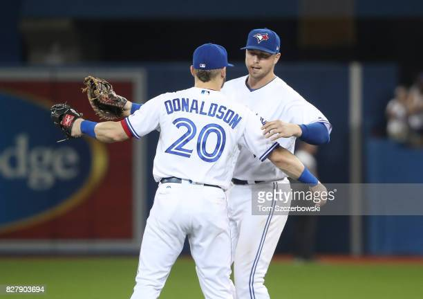 Josh Donaldson of the Toronto Blue Jays celebrates their victory with Justin Smoak during MLB game action against the New York Yankees at Rogers...