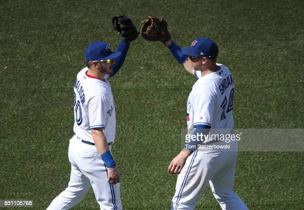 Josh Donaldson of the Toronto Blue Jays celebrates their victory with Justin Smoak during MLB game action against the Pittsburgh Pirates at Rogers...