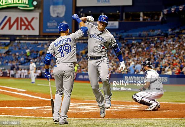Josh Donaldson of the Toronto Blue Jays celebrates with teammate Jose Bautista after hitting a home run off of Drew Smyly of the Tampa Bay Rays...