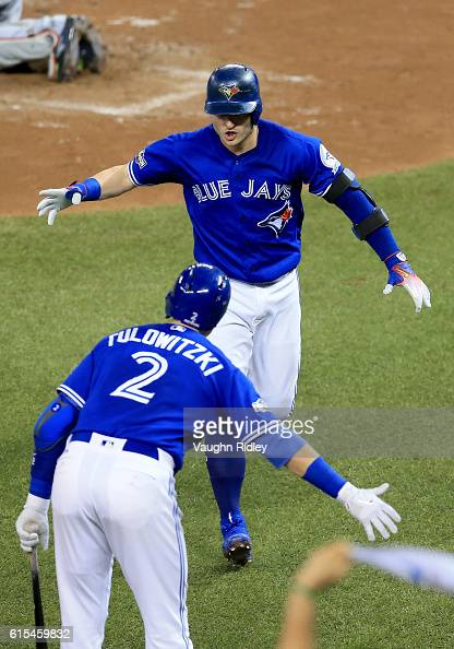 Josh Donaldson of the Toronto Blue Jays celebrates with teammate Troy Tulowitzki after hitting a solo home run in the third inning against Corey...