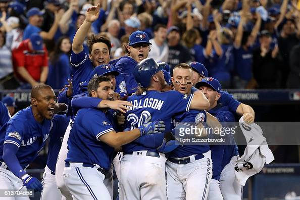 Josh Donaldson of the Toronto Blue Jays celebrates with teammates after the Toronto Blue Jays defeated the Texas Rangers 76 in ten innings during...