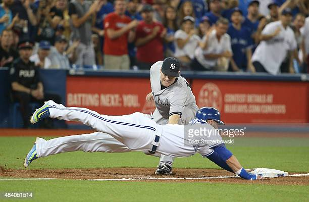 Josh Donaldson of the Toronto Blue Jays dives back safely to third base in the third inning during MLB game action as Chase Headley of the New York...