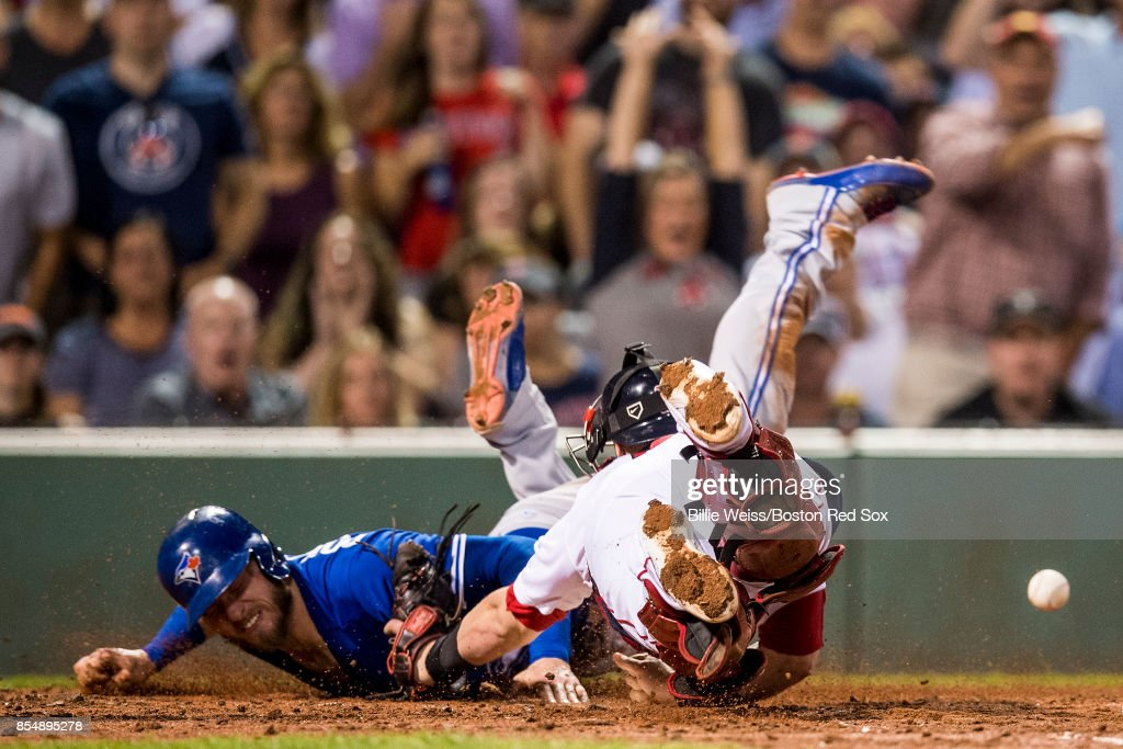 Josh Donaldson #20 of the Toronto Blue Jays evades the tag of Christian Vazquez #7 of the Boston Red Sox as he scores during the third inning of a game on September 27, 2017 at Fenway Park in Boston, Massachusetts.