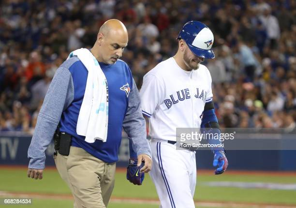 Josh Donaldson of the Toronto Blue Jays exits the game with trainer George Poulos after hitting an RBI double in the sixth inning during MLB game...